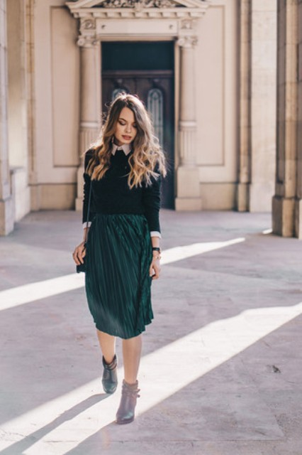 With emerald pleated knee-length skirt, chain strap bag and ankle boots