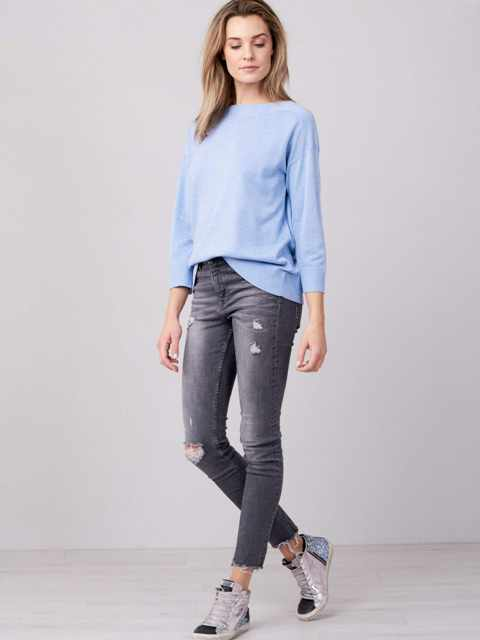 With gray distressed skinny jeans and metallic sneakers
