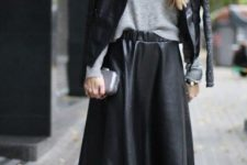 With gray loose shirt, black leather jacket, silver clutch and black pumps