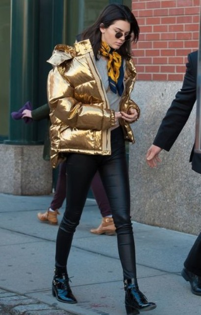 With gray t-shirt, black leather skinny trousers, black low heeled boots and yellow and blue scarf