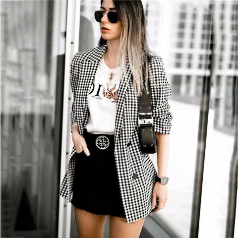 With labeled t-shirt, black leather bag and black belted mini skirt