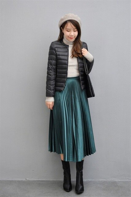 With light gray beret, light gray turtleneck, chain strap bag, emerald pleated midi skirt and black mid calf boots