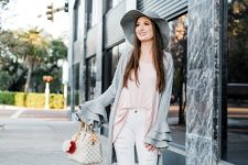 With pale pink loose shirt, printed bag, white distressed pants, lace up shoes and gray hat