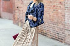 With top, metallic pleated midi skirt, purple clutch and black shoes