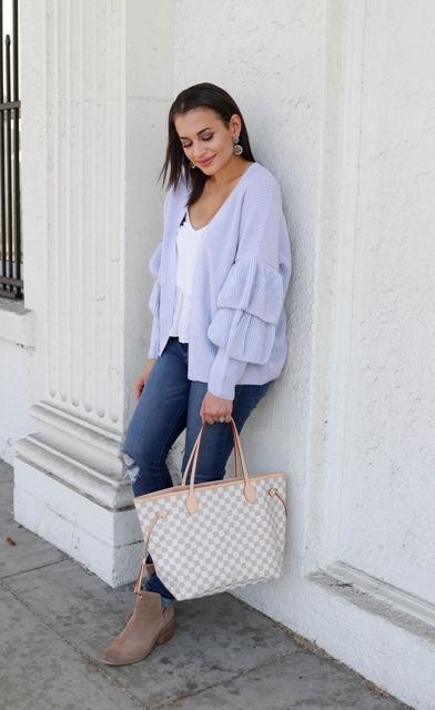 With white V-neck top, distressed jeans, beige suede ankle boots and printed tote bag