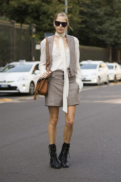 With white blouse, checked vest, checked shorts and brown bag