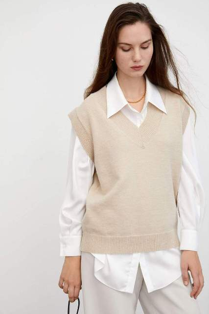 With white button down shirt, beige pants and bag