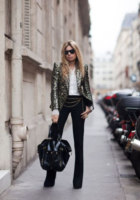 With white button down shirt, black flare pants, chain belt and black tote bag
