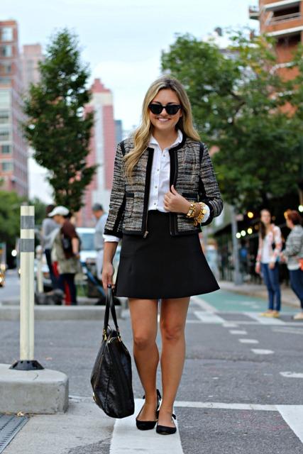 With white button down shirt, black skater mini skirt, sunglasses, black tote bag and black flat shoes