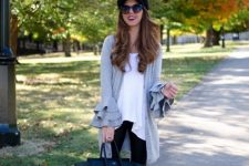 With white long blouse, black cap, black leggings, tote bag and heeled boots
