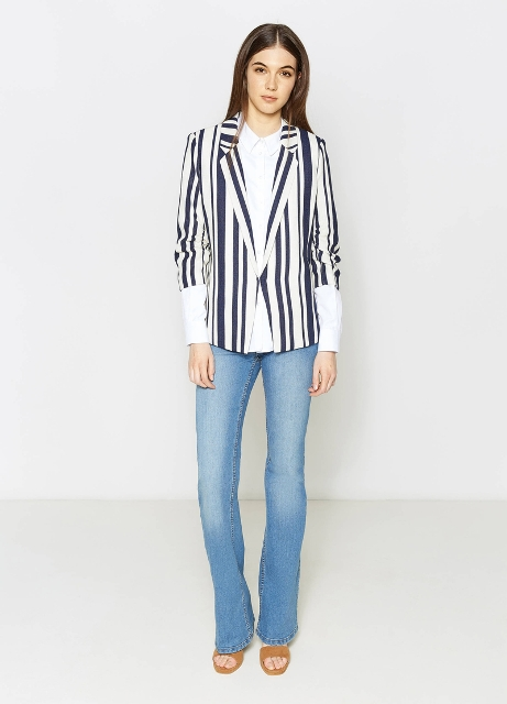 With white long sleeved button down shirt, light blue flare jeans and brown sandals