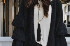 With white loose sweater, clutch and dark gray jeans