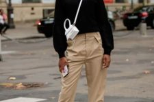 With white mini crossbody bag, beige high-waisted trousers, sunglasses and white sneakers