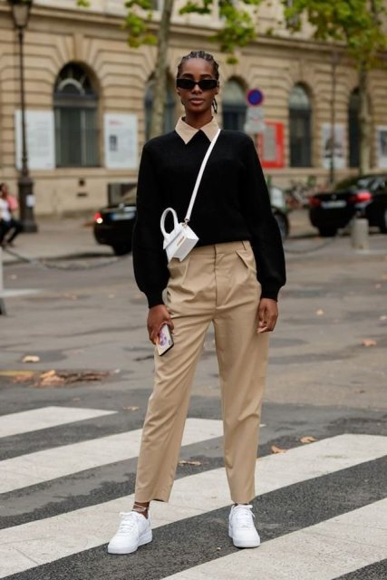 With white mini crossbody bag, beige high waisted trousers, sunglasses and white sneakers