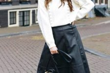 With white oversized sweater, leopard printed tassel bag and black boots