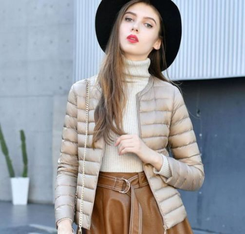 With white turtleneck sweater, black wide brim hat and brown leather belted skirt