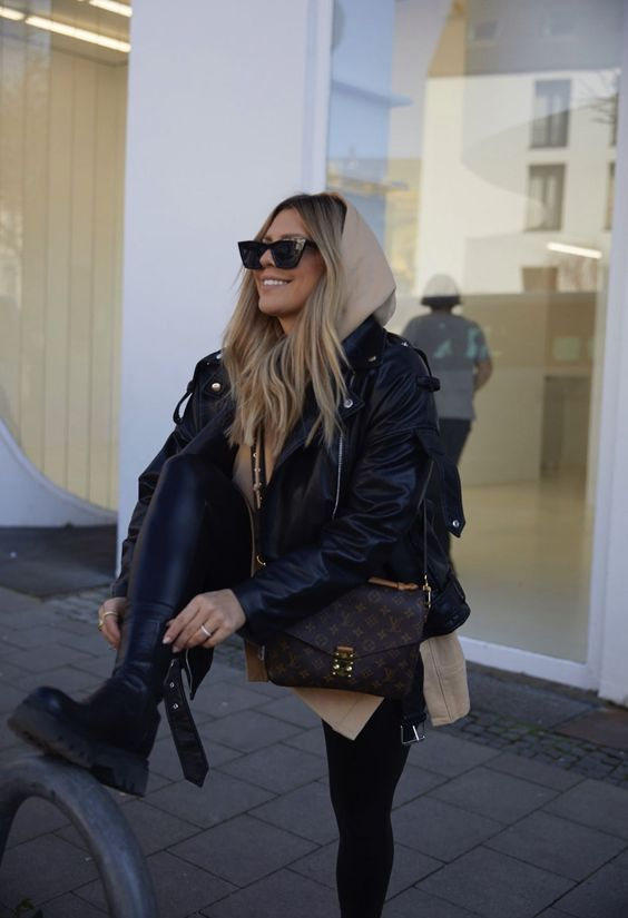 a beige oversized hoodie, a black leather jacket, black leggings, black boots and a brown printed bag