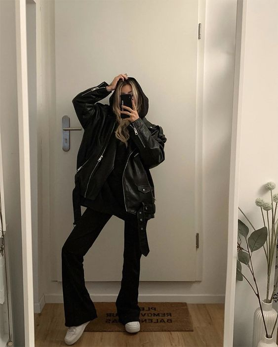 a black hoodie, flare trousers, white sneakers and an oversized black leather jacket