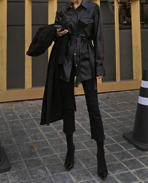 a black leather shirt with a sash, black cropped flare jeans, black sock boots and a black coat on top