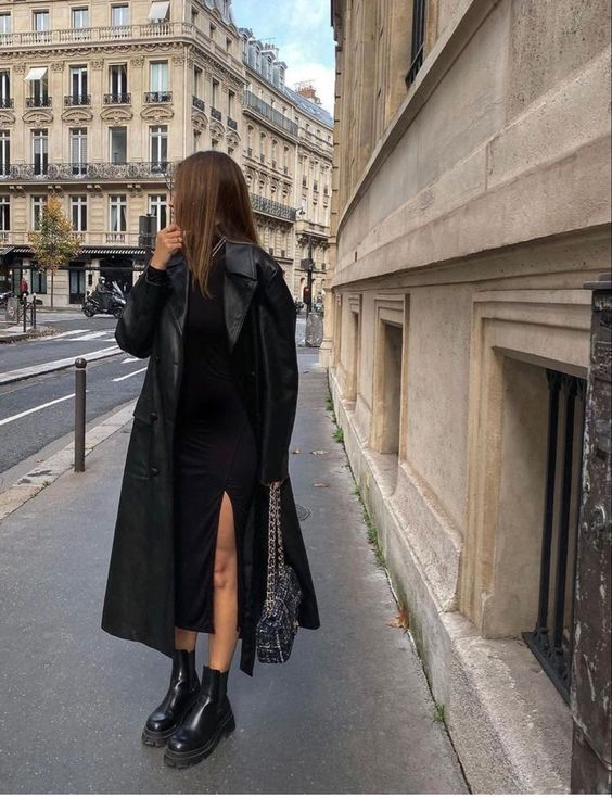 a black midi dress with a side slit, chunky boots, a leather trench and a grey and white printed bag