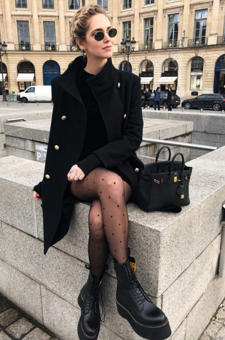 a black mini dress, combat boots and pritned tights, a black knee coat and a black bag for a girlish look