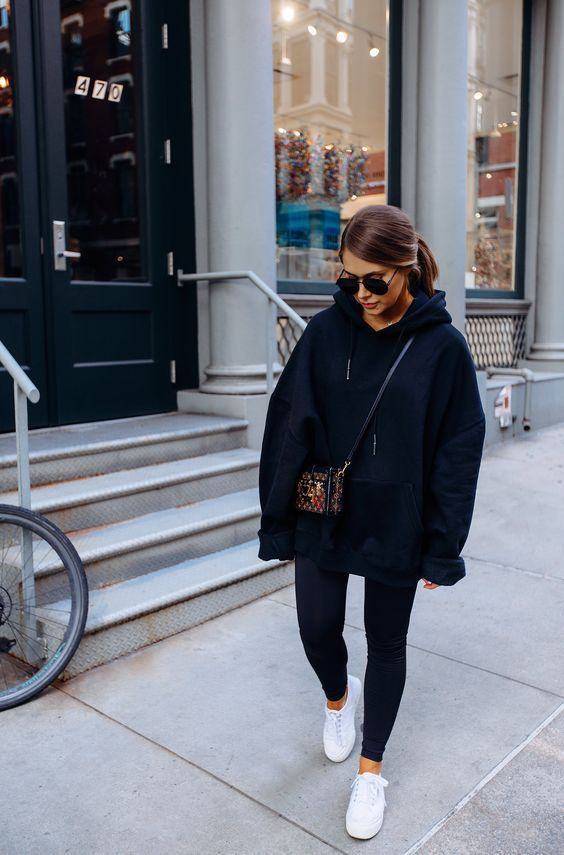 a black oversized hoodie, black leggings, a colorful printed bag and white sneakers to wear tight now