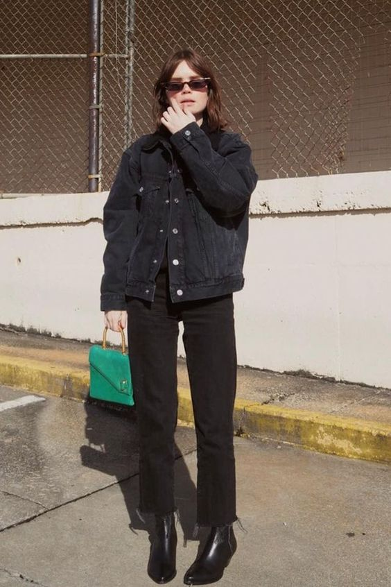 a black top, an oversized denim jacket, black jeans and boots and en emeral and gold mini bag for a colorful accent