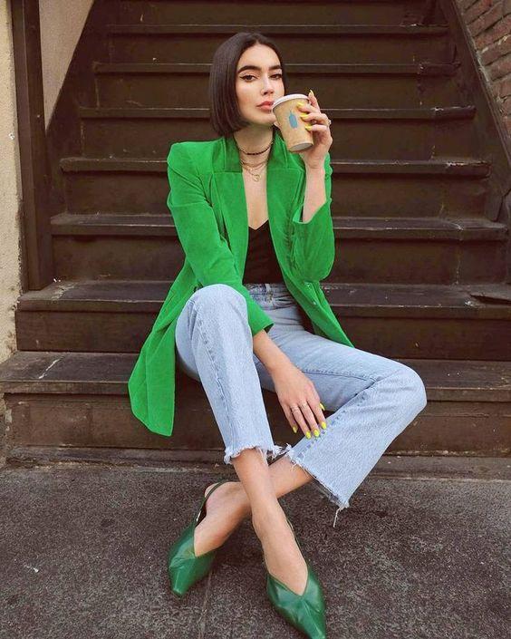 a black top, blue jeans, a bold green long blazer, green slingbacks for a creative work look