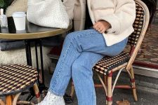 a black turtleneck, a creamy faux fur jacket, blue jeans, white sneakers and a creamy woven clutch is cool
