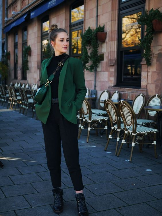 a black turtleneck, black cropped trousers, boots, a green blazer and a green mini bag for working