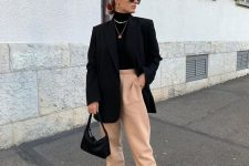 a black turtleneck, peachy sweatpants, black sneakers, an oversized blazer, layered necklaces and a black bag