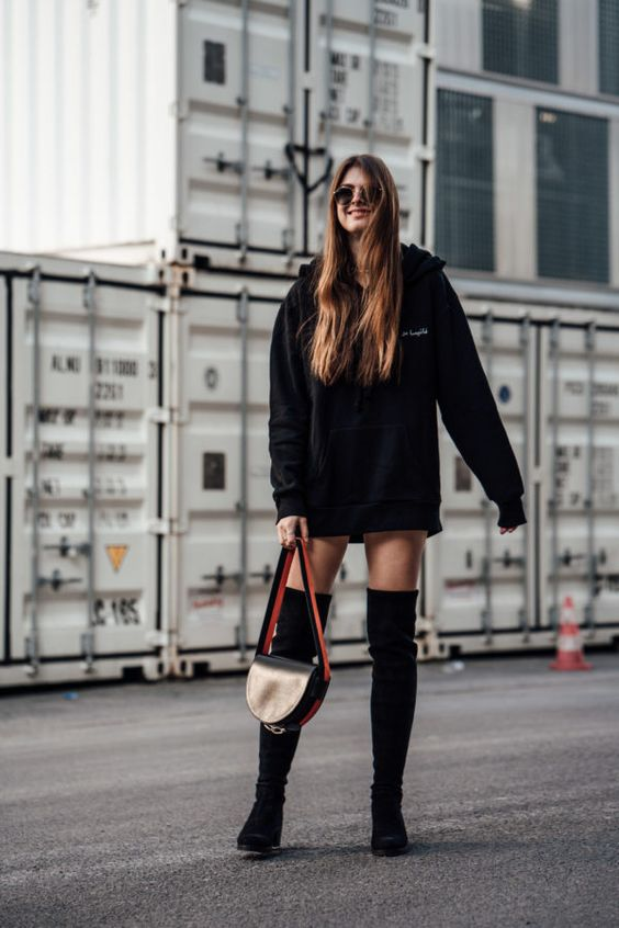 a bold and sexy look with an oversized hoodie as a dress, over the knee boots and a black bag for a daring look