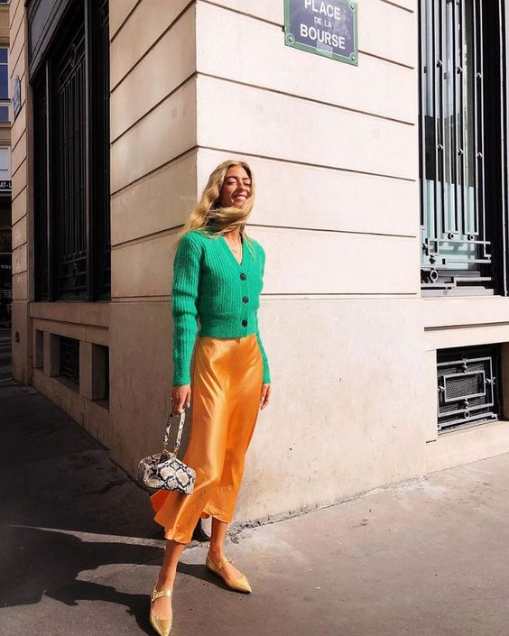 a bright and stylish outfit with an apple green cardigan, a marigold slip skirt, yellow Mary Jane shoes and a snakeskin print bag