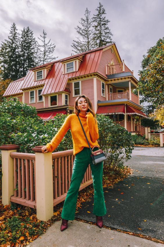 a bright fall look with a marigold turtleneck, emerald flare jeans, purple boots and a two tone bag