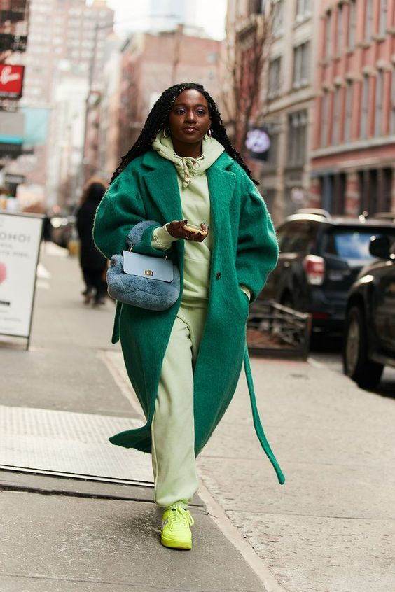 a bright fall outfit with a neon grene hoodie and pants, neon yellow sneakers, an emerald fuzzy coat and a blue faux fur bag