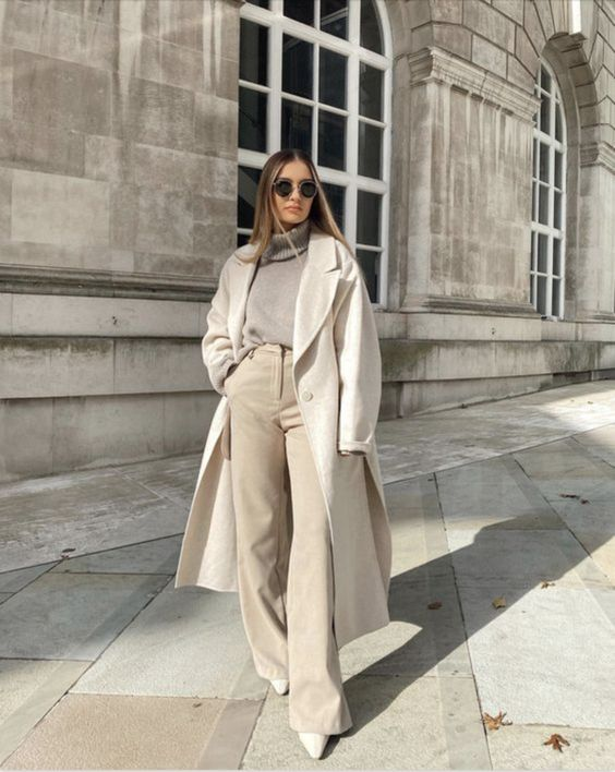 a chic all-neutral outfit with a grey turtleneck, creamy pants, a creamy midi coat, white booties for late fall or winter