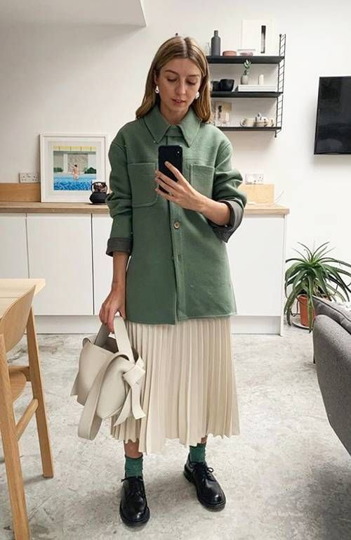 a chic work outfit with a white pleated midi skirt, a green shirt jacket, green socks, man style shoes and a neutral bag