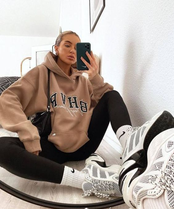 a comfy sporty outfit with a tan oversized hoodie, black leggings, white socks and trainers plus a black bag for every day