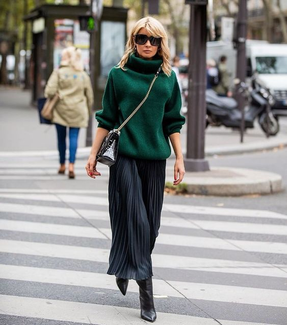 a cozy fall outfit with a dark green oversized turtlenec sweater, a black pleated maxi, black boots and a black bag on chain