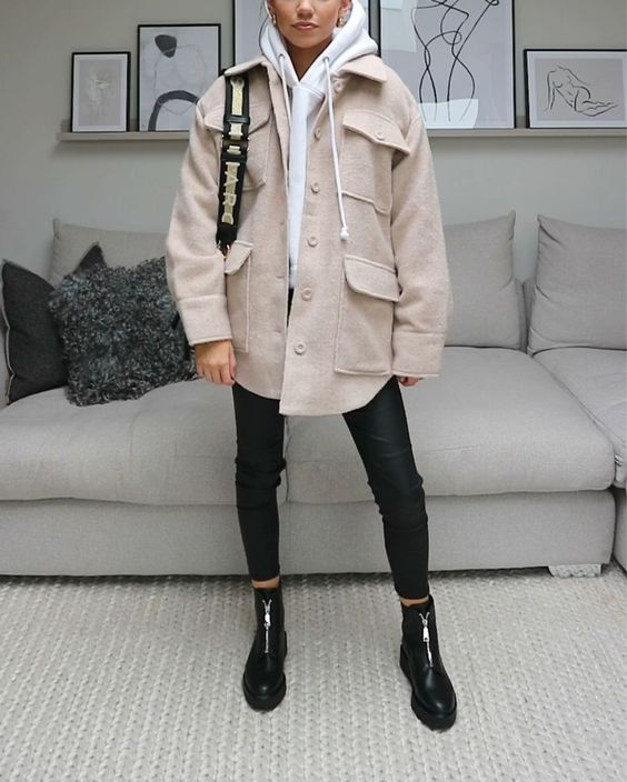 a creamy hoodie, a tan shirt jacket, black leather pants, black zip boots, a black bag for a cool and cozy fall outfit