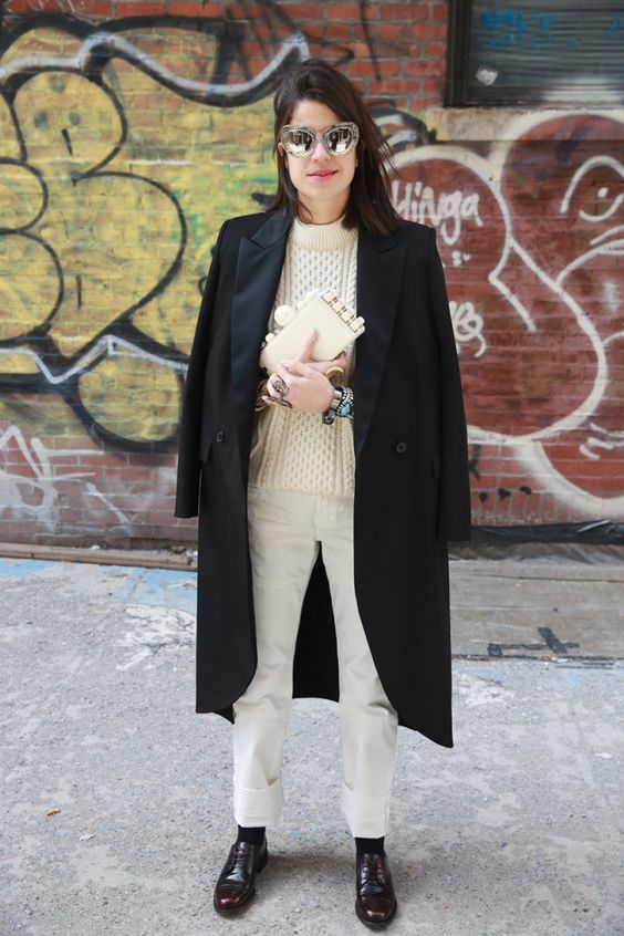 a creamy patterned sweater, white jeans, burgundy shoes and black socks plus a black midi coat and a creamy clutch