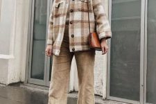 a creamy sweater, a neutral plaid shirt jacket, tan corduroy trousers, brown boots and a brown bag