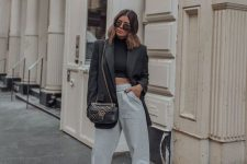 a creative look with a black cropped turtleneck, grey sweatpants, black lace up shoes, an oversized blazer and a black bag