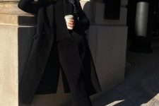 a fabulous total black look with a fitting black maxi dress, a black coat, man-style shoes and black socks plus a black bag