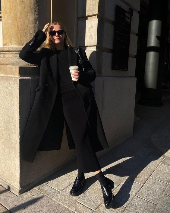 a fabulous total black look with a fitting black maxi dress, a black coat, man style shoes and black socks plus a black bag