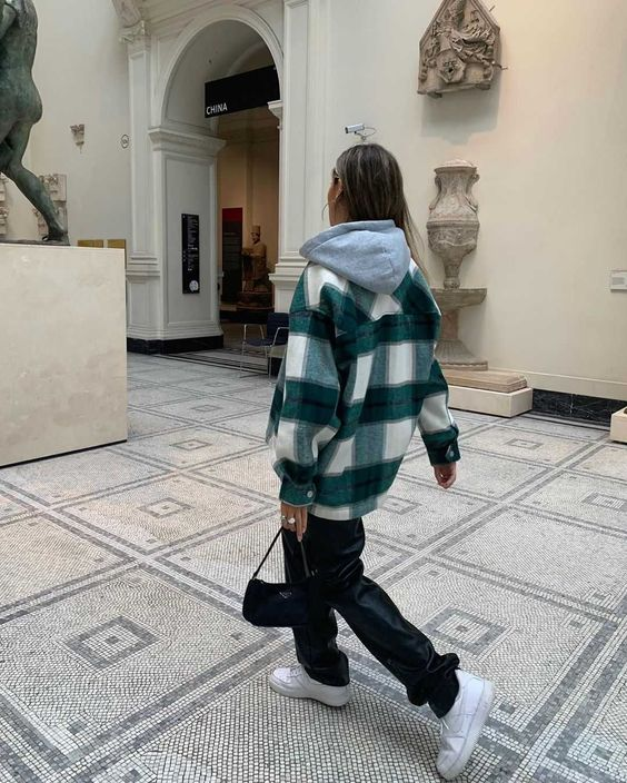 a grey oversized hoodie, a white and green plaid shirt jacket, black leather trousers, white sneakers and a black bag