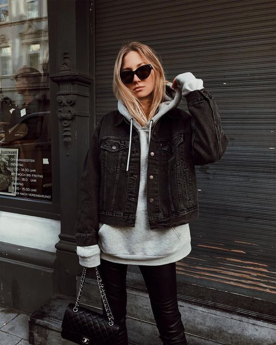 a grey oversized hoodie, black leather leggings, a black cropped denim jacket, a black bag for a stylish look