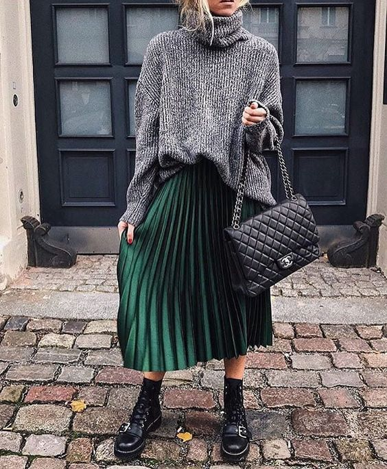 a grey turtelenck sweater, a green pleated midi skirt, black combat boots and a black bag for fall