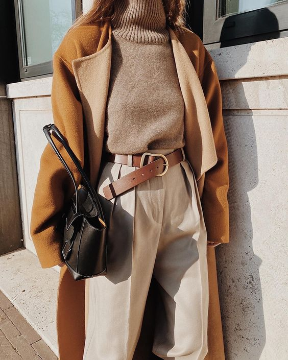 a grey turtleneck, creamy high waisted pants, a brown belt, an amber coat, a black bag for the fall