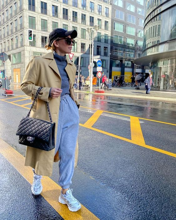 a grey turtleneck, grey sweatpants, grey trainers, a beige trench, a black cap and a black bag for maximal comfort